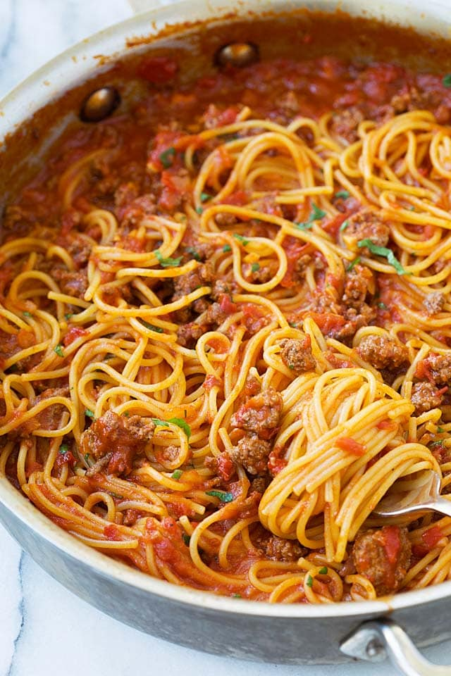 Close up picture of easy spaghetti pasta with orange-color tomato meat sauce, ready to be eaten.
