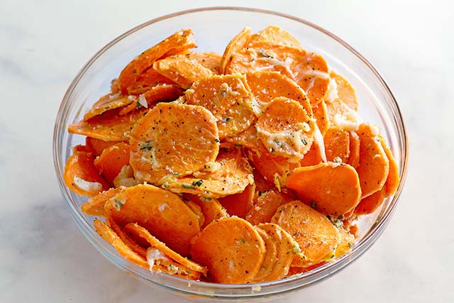 Sliced sweet potatoes coated with butter.