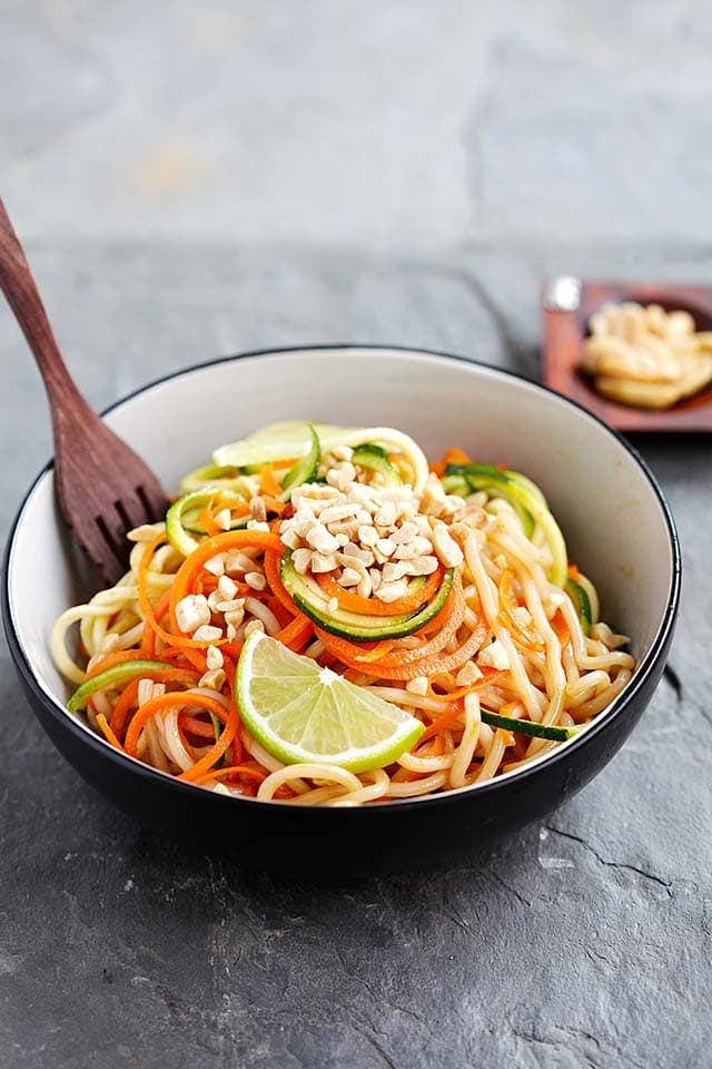 Zucchini noodles with Thai peanut sauce served in a bowl, ready to be eaten.