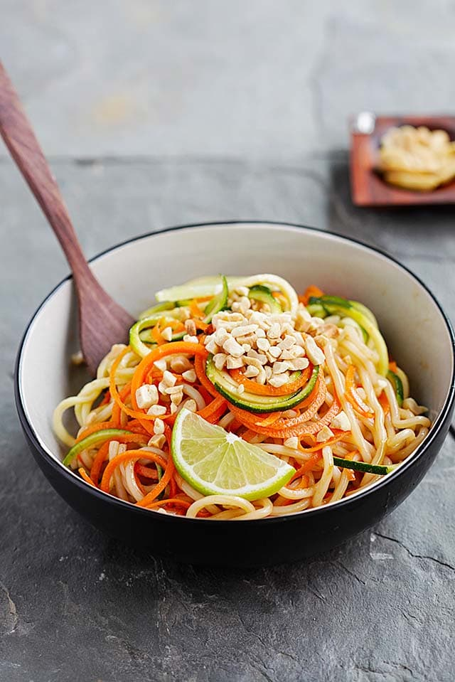 Thai Peanut Zucchini Noodles with carrots and peanut sauce, topped with crushed peanuts.