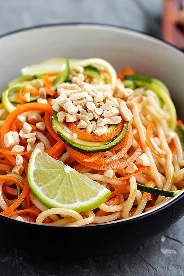 Close up shot of Thai peanut zucchini noodles served in a bowl, topped with crushed peanuts.