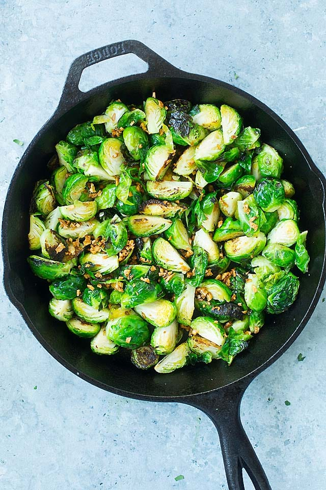 Sauteed Brussels Sprouts in a cast-iron skillet with crispy garlic.