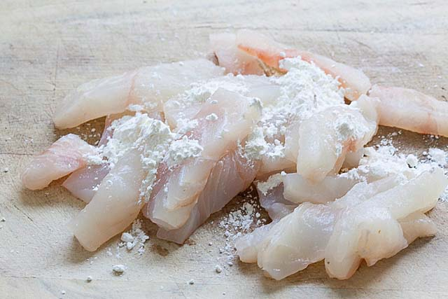 Pacific halibut cut into small pieces on a cutting board, ready to cook.