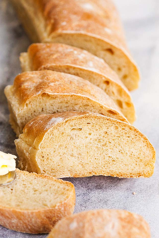 Close up of baguette, with golden brown crusty exterior and soft white interior.