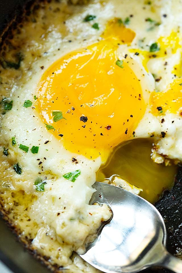 Parmesan eggs with runny egg yolk in a skillet.