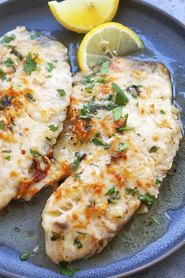 Tilapia recipe with lemon and Parmesan cheese, served on a plate.