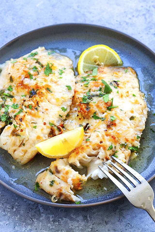 Tilapia fish on a plate and served with fork and lemon wedges.