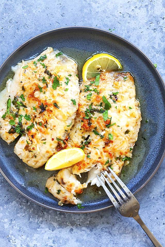 Top down picture of Lemon Parmesan crusted tilapia on a serving plate, topped with herbs and fresh lemon wedges.