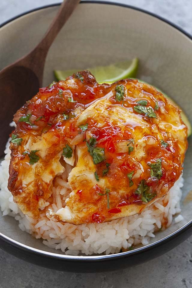 Egg meals with fried eggs and sweet chili sauce in a bowl.
