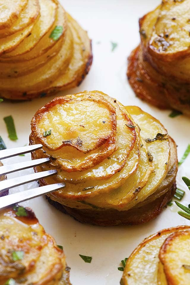 Potato stacks with a fork on a plate, ready to be served.