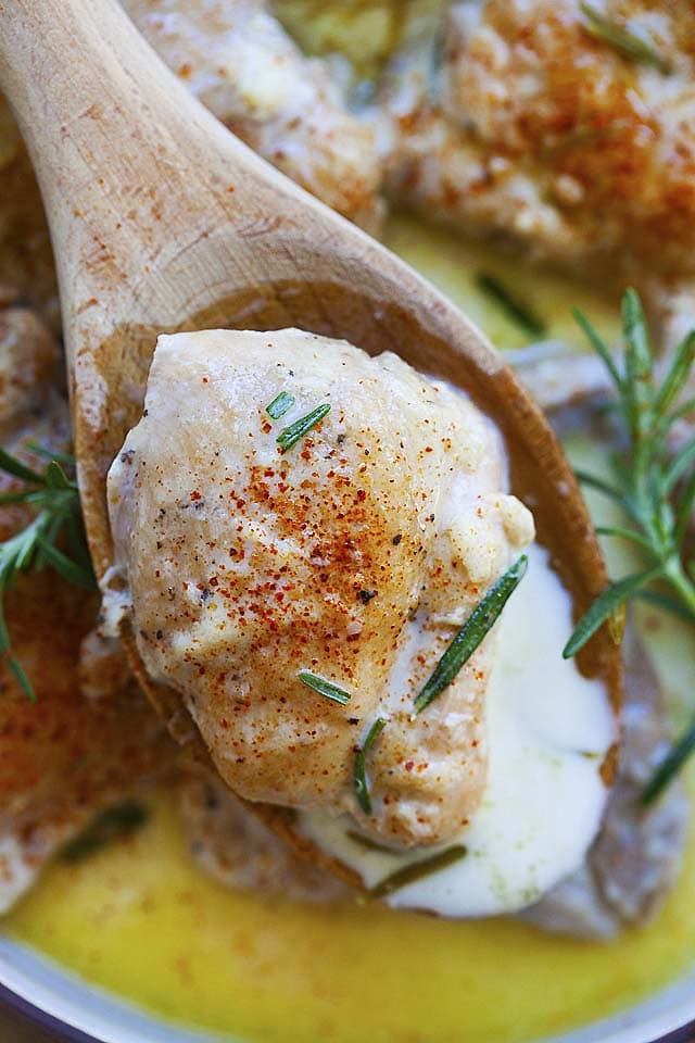 Top down picture of a boneless and skinless chicken thigh with creamy garlic sauce, served with a wooden spoon.