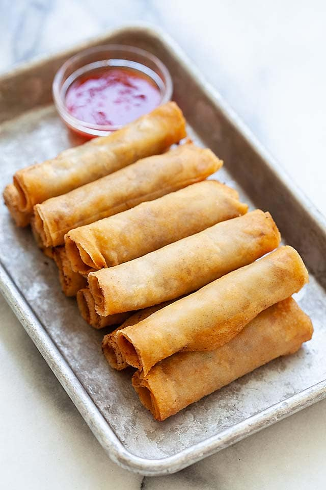 Lumpia or Filipino fried spring rolls on a plate with lumpia sauce, ready to be served.