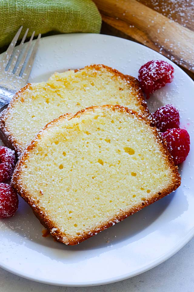 Two pieces of cream cheese pound cake on a plate with dessert fork, ready to be served.