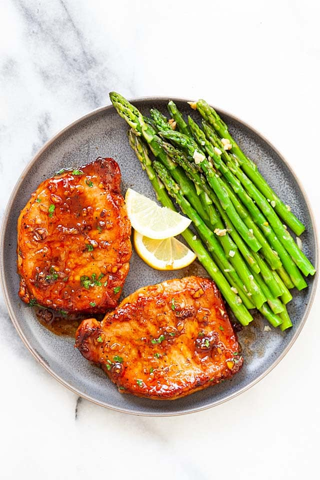 Boneless pork chops (center-cut boneless pork chops) with asparagus on a plate.