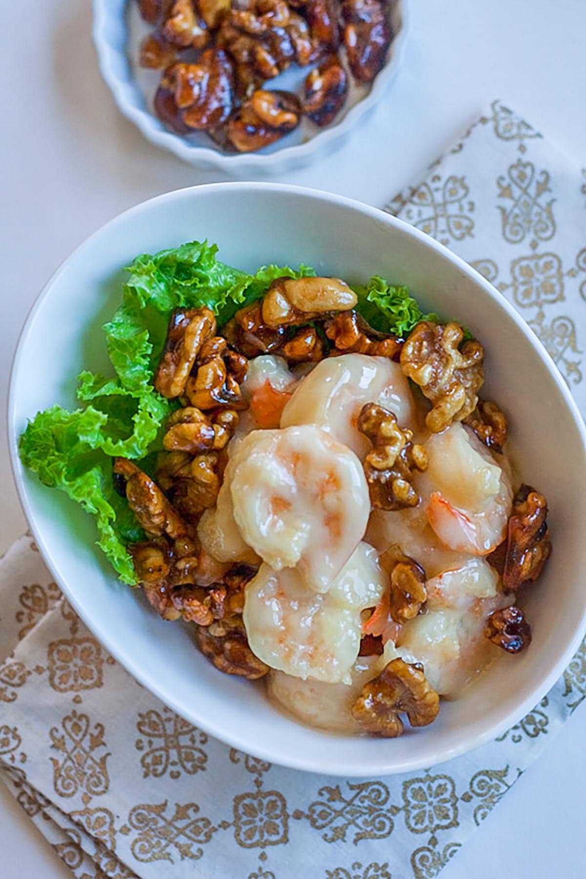 Honey walnut shrimp in a white bowl, with candied walnuts, ready to be served.