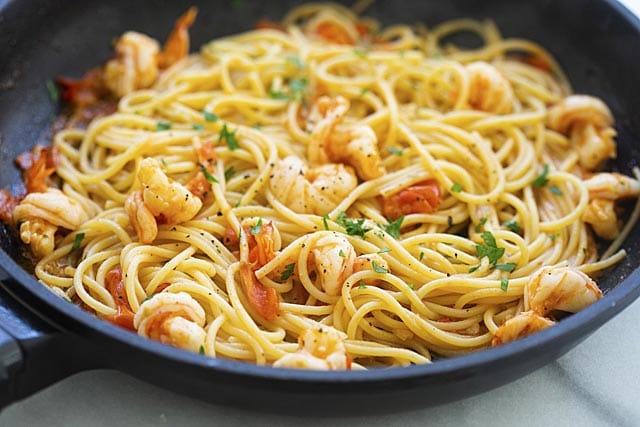 Shrimp pasta cooking in skillet.
