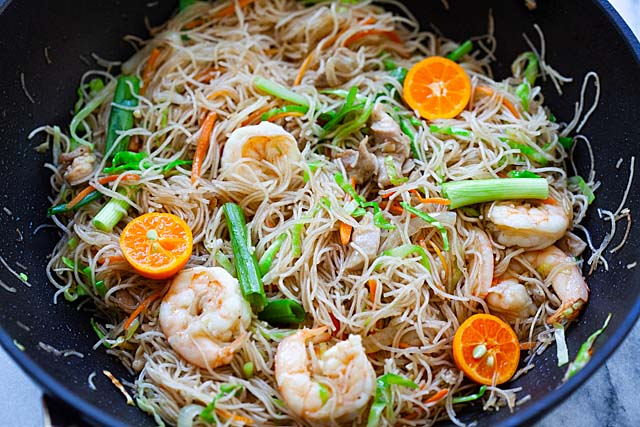 Shrimp pancit recipe with chicken and vegetables in a skillet.