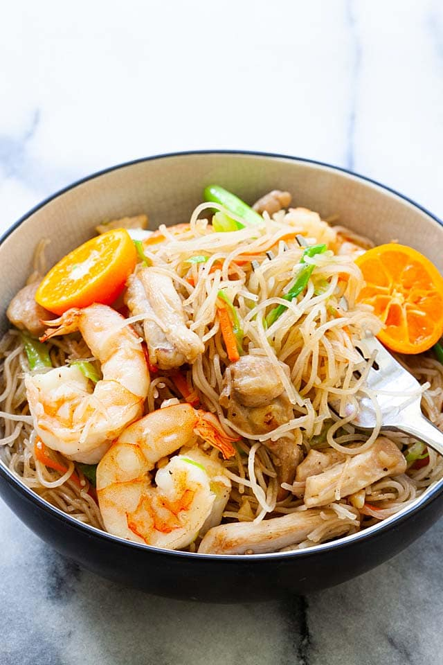 A fork picking up Filipino noodles or pancit in a bowl.