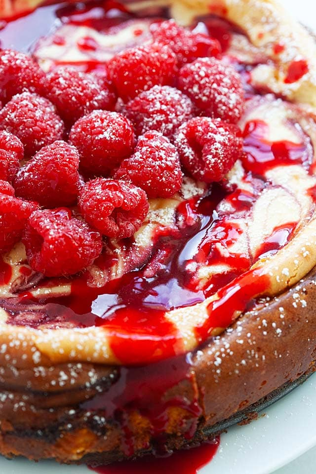 Raspberry cheesecake with topping of raspberry sauce, dripping down the cheesecake.