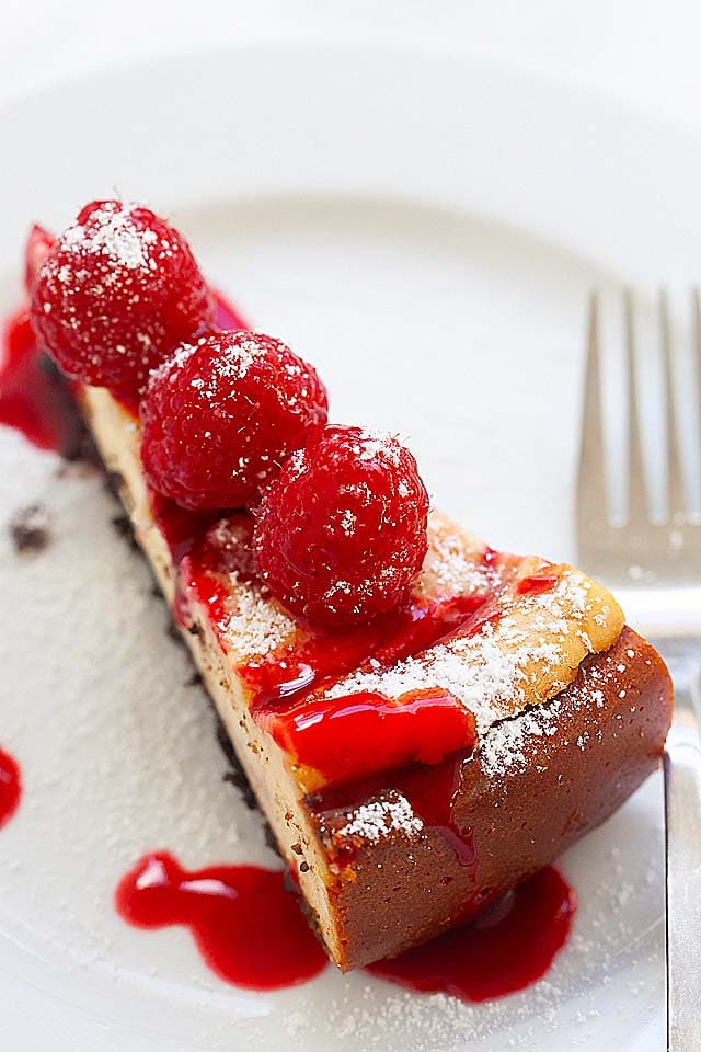 Easy raspberry cheesecake recipe yields a slice of raspberry cheesecake on a plate with raspberry sauce topping.
