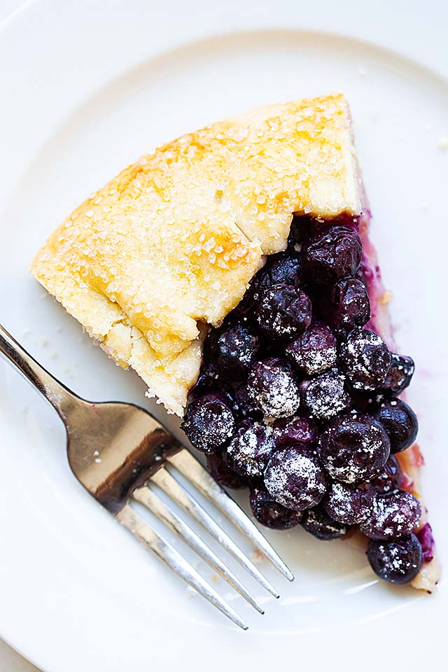 Blueberry galette on a white plate with a fork.