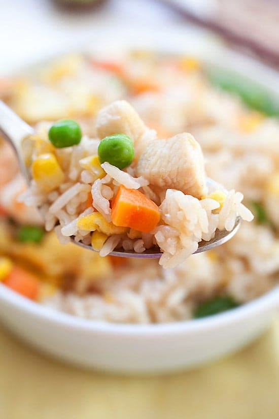 Chinese takeout egg fried rice with chicken, shrimp and vegetable on a spoon.