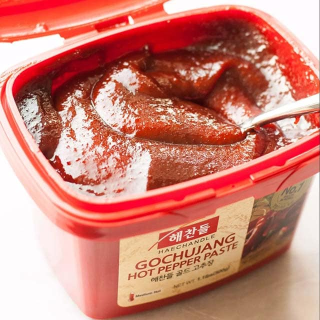 Gochujang in a plastic tub, used as a sauce for Korean fried chicken.