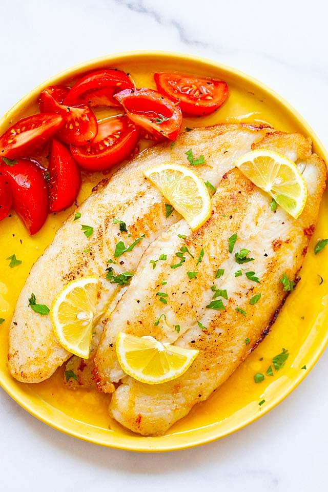 Swai fish with lemon butter sauce on a plate, ready to serve.