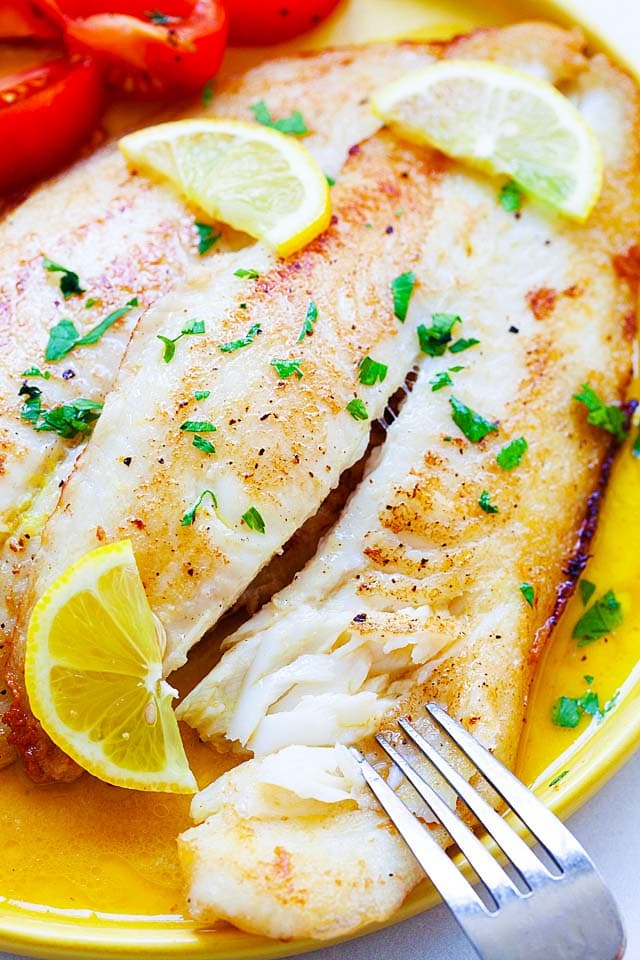 Pan fried fish with lemon butter sauce, served on a plate with a fork.