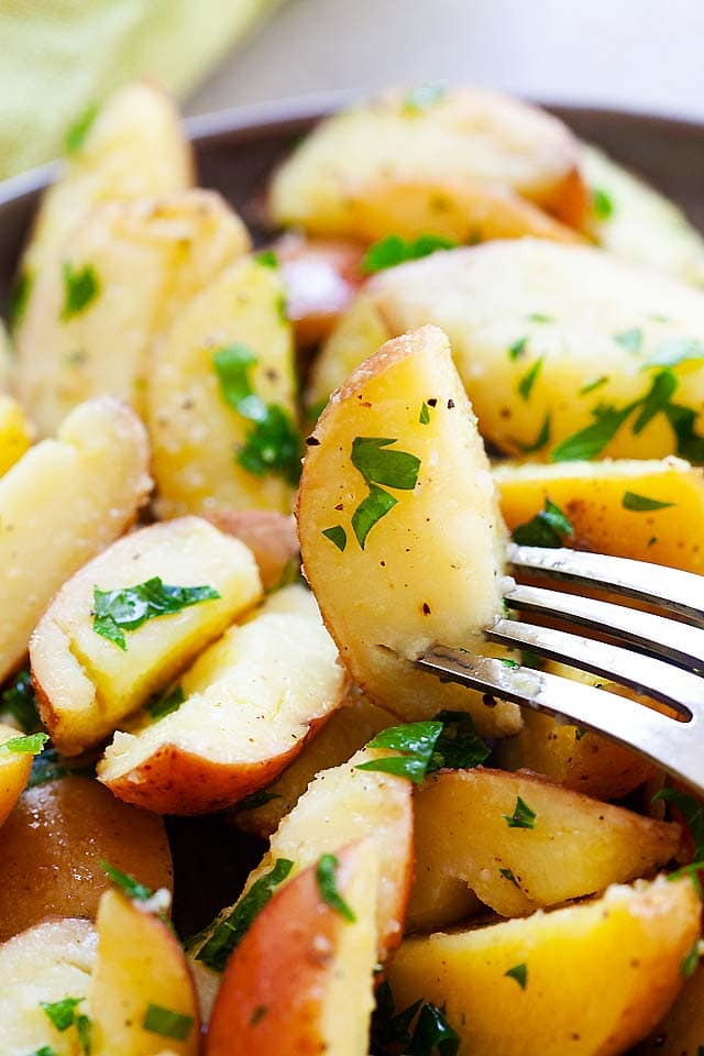 Boiled potatoes with parsley, butter, salt and black pepper, ready to serve.