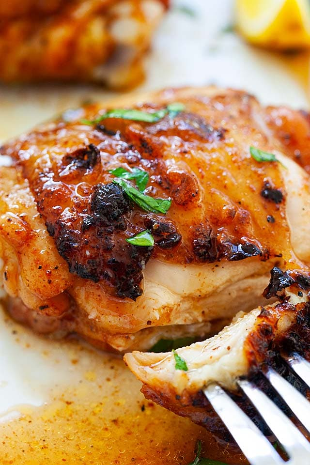 BBQ chicken thigh with a fork, with juicy oozing out.