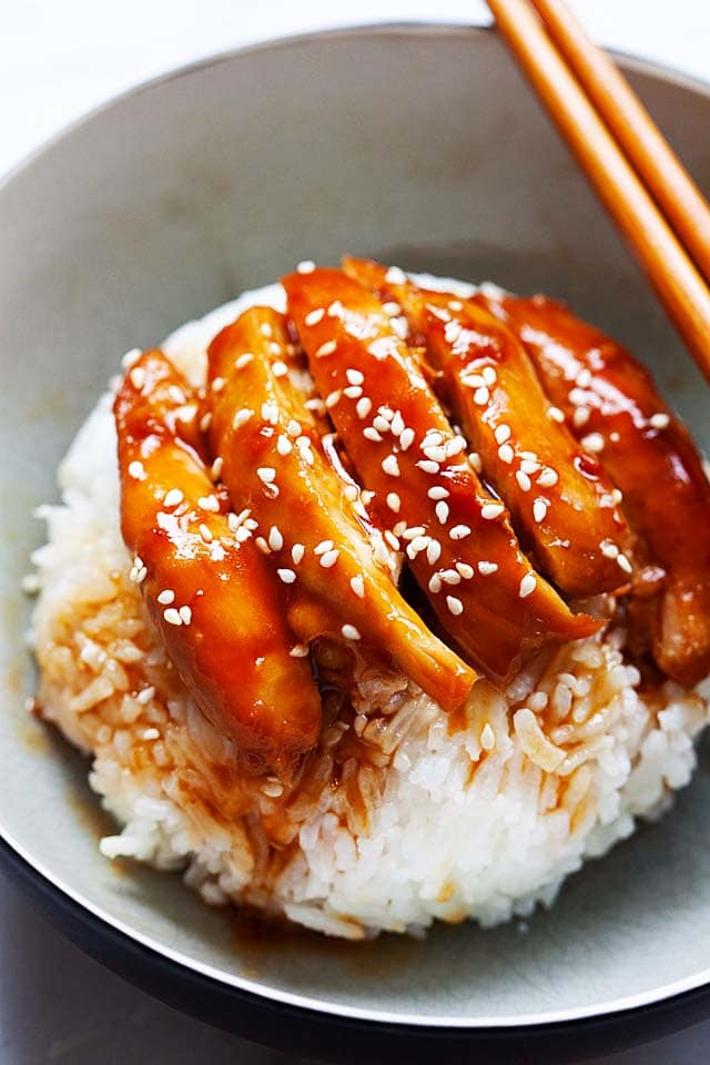 Chicken teriyaki with steamed rice in a bowl with a pair of chopsticks.