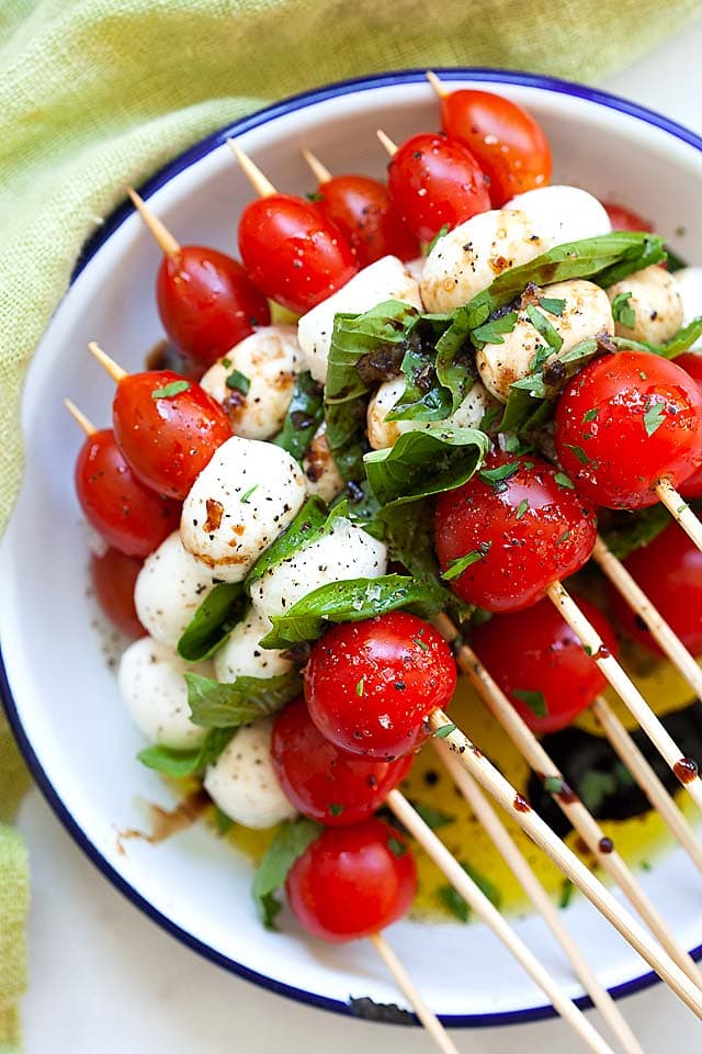 Caprese salad skewers, made with tomatoes, mozzarella, and basil leaves.