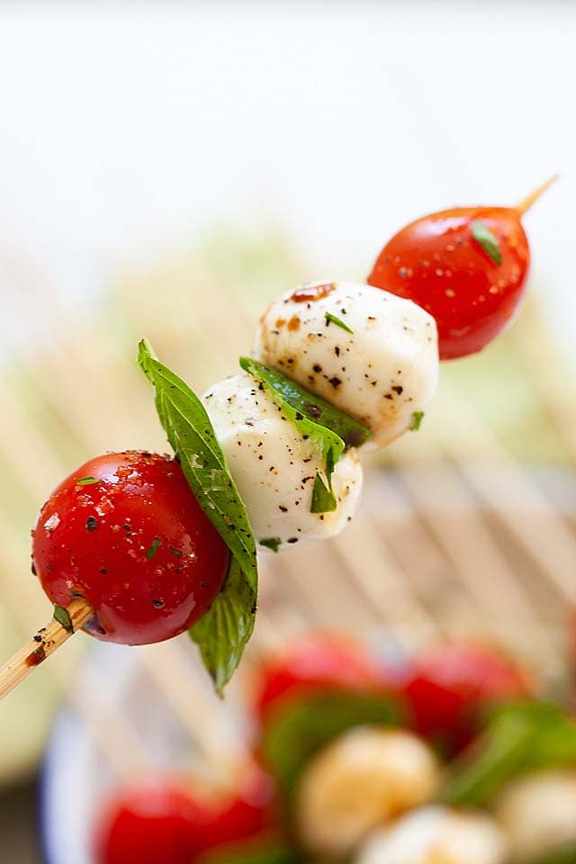 A close up of a single stick of Caprese skewer.