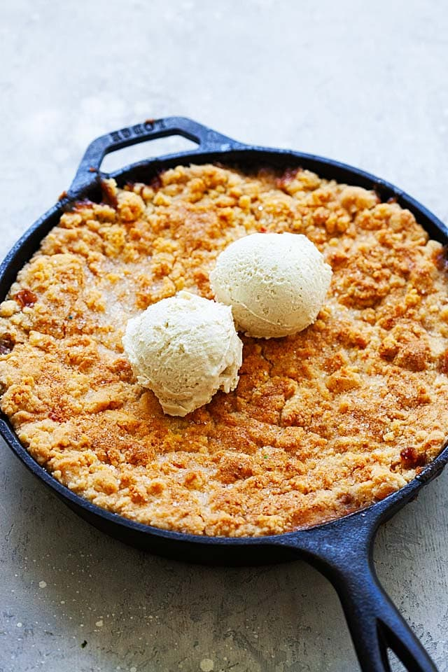 Easy peach cobbler topped with two scoops of ice cream.