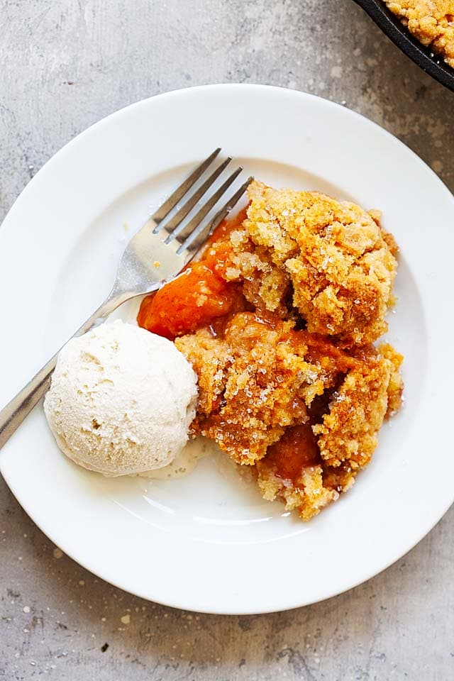 Homemade peach cobbler on a white plate, ready to serve.