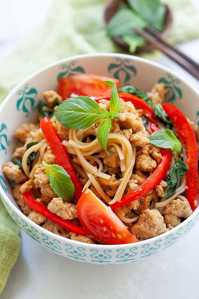 Drunken noodles in a bowl, ready to serve with a pair of chopsticks.