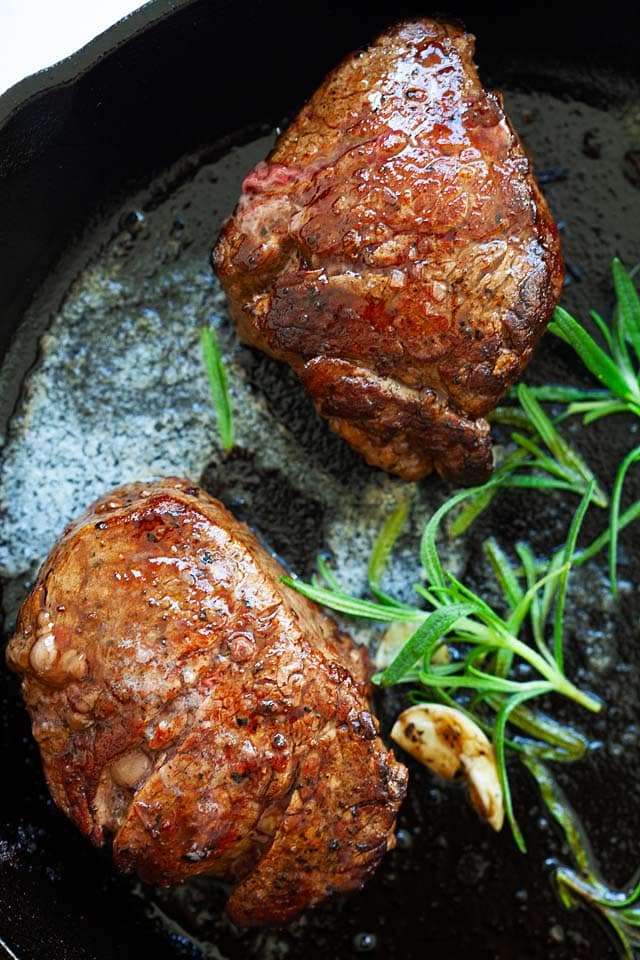Filet mignon recipe with butter, garlic and rosemary, cooked on a skillet on stove top.