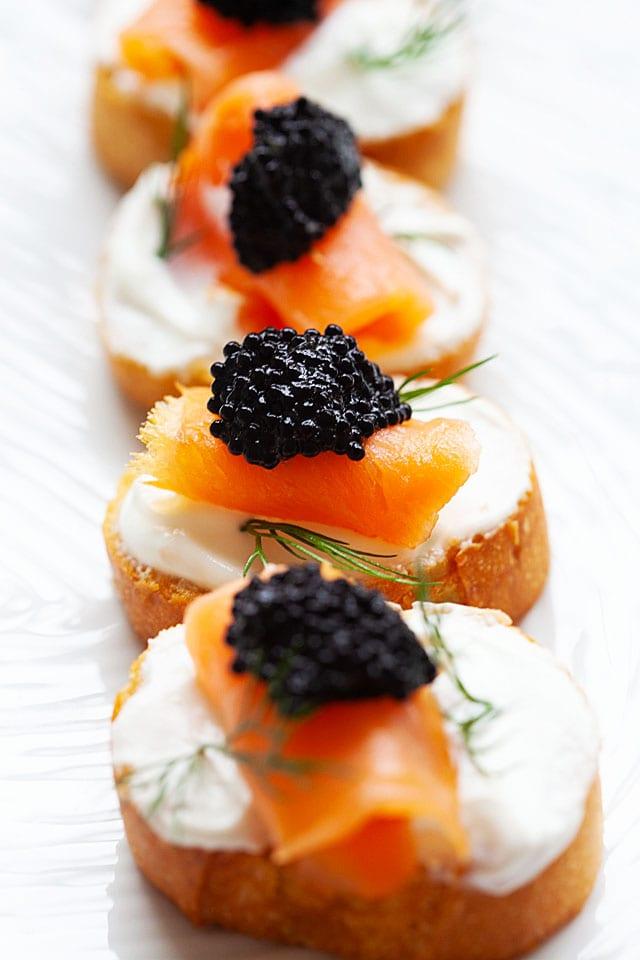 Crostini with sour cream, smoked salmon and caviar topping.