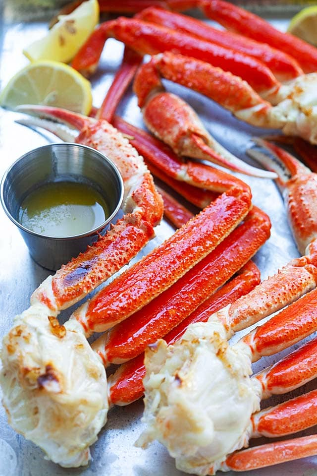 Snow crab legs served with melted butter and lemon wedges.