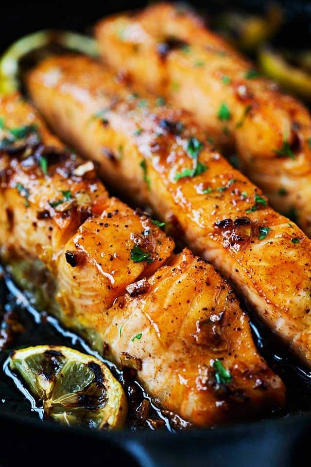 Salmon fillet with honey garlic sauce cooked on stove.