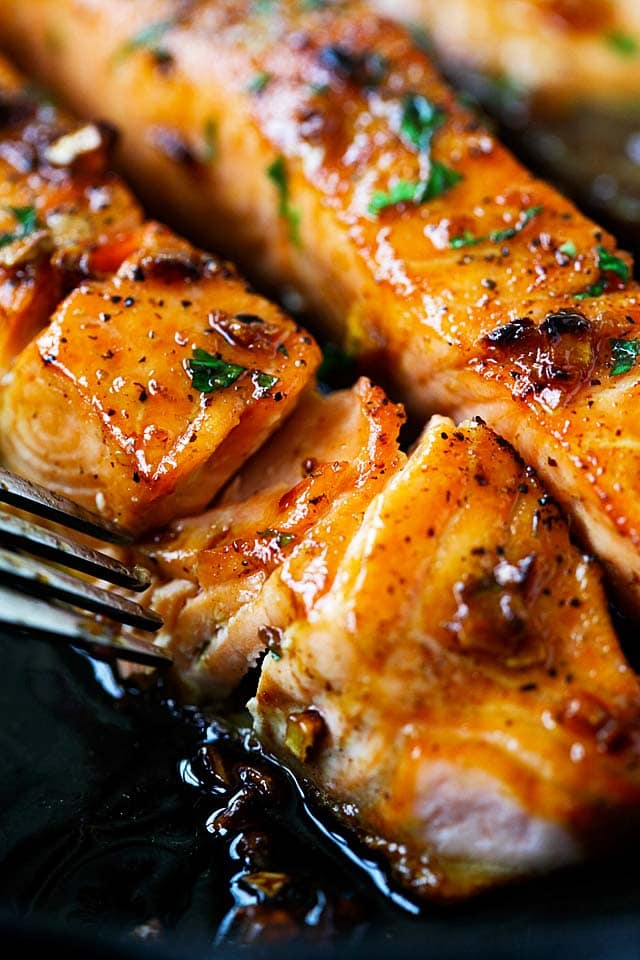 Salmon recipe with honey garlic sauce on a skillet.
