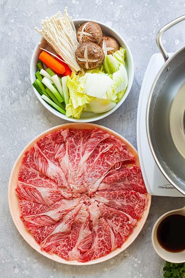 Shabu shabu recipe with beef, vegetables, mushrooms and carrots.