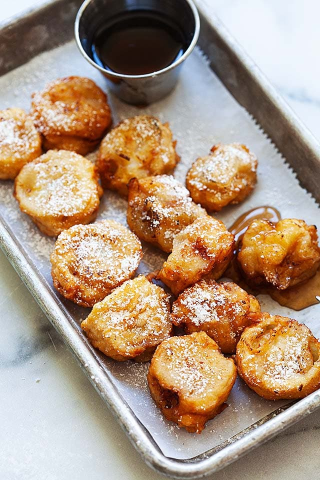 Deep fried bananas with maple syrup on a plate.