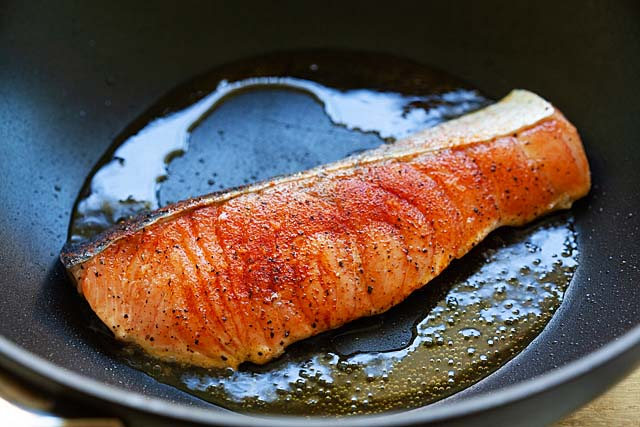 Cooking salmon in a pan on the stove.