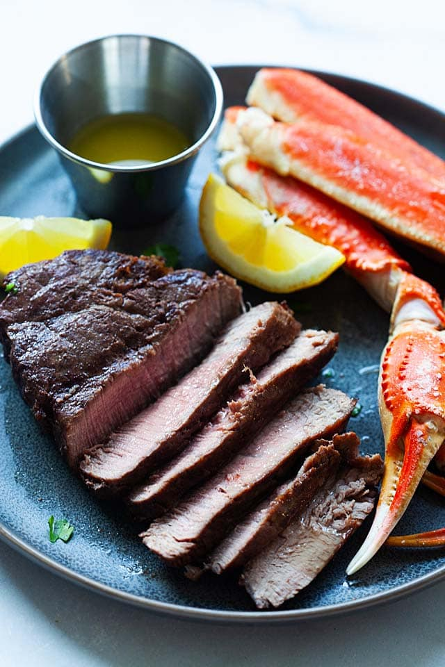 Surf and turf recipe with grilled steak and steamed crab legs.