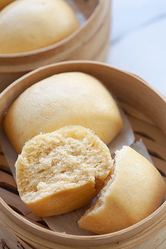 Mantou buns steamed in a bamboo basket.