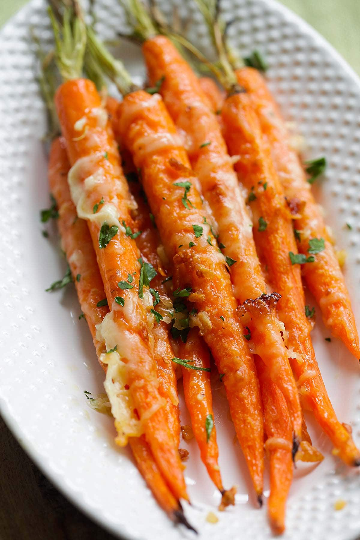 One of the best roasted carrot recipes made with carrot tops, garlic, butter and Parmesan cheese on a plate.