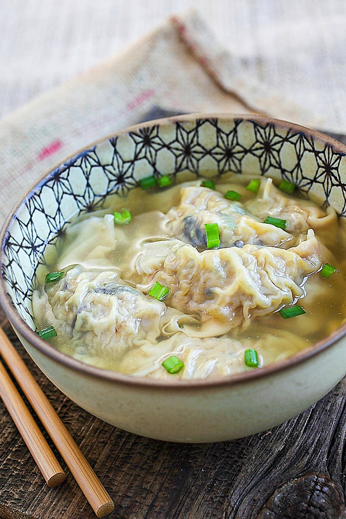Delicious and easy homemade Chinese pork dumplings soup served in a bowl.