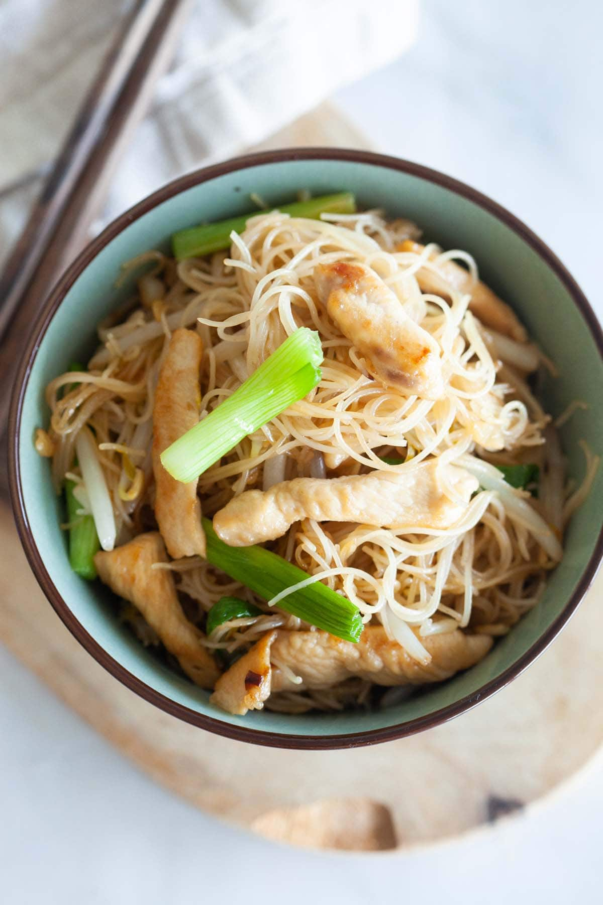 Rice noodles with chicken in a bowl.